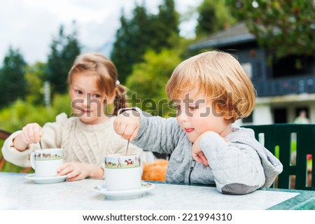 Adorable children drinking hot chocolate outdoors, spending good time on vacation in alpine mountains - stock photo
