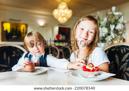 Adorable children eating cakes in a beautiful cafe - stock photo