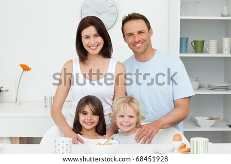 Adorable children posing with their parents in the kitchen during breakfast