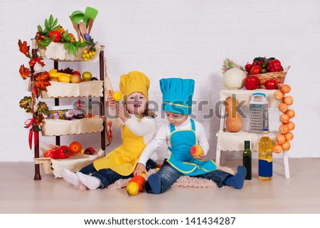 adorable children prepare in kitchen. little cute children in costume of Cook. funny cooks with vegetables in studio.Pretty beautiful boy and girl cook soup.baby boy. baby girl