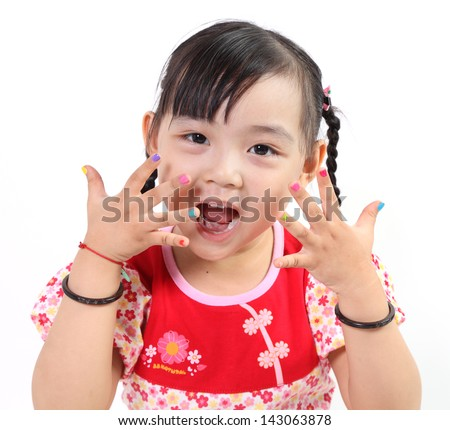 Adorable Chinese little girl with multi-coloured manicure - stock photo