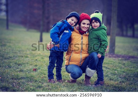 Adorable colorful portrait of a mother with her two boys, outdoor, vintage filter - stock photo