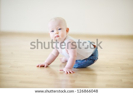 Adorable crawling baby girl on a floor