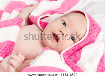 Adorable curious baby girl in pink blanket looking at the camera - stock photo