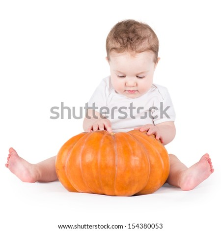 Adorable curious baby girl playing with a big pumpkin on white background