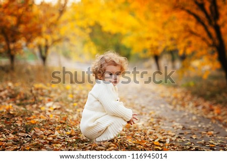 Adorable curly girl walking in autumn park - stock photo