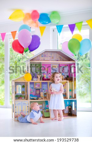 Adorable curly toddler girl in a white dress and her little baby brother playing together with a birthday present - huge doll house in a white living room with big windows decorated with balloons - stock photo