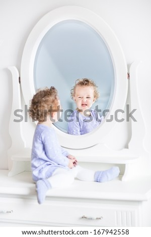 Adorable curly toddler girl making funny faces watching her reflection in a beautiful white mirror  - stock photo