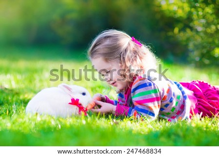 Adorable curly toddler girl playing with a real rabbit in a sunny summer garden, child feeding bunny a carrot.