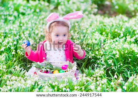 Adorable curly toddler girl wearing bunny ears playing with Easter eggs in a white basket sitting in a sunny garden with first white spring flowers  - stock photo