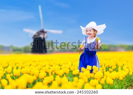 Adorable curly toddler girl wearing Dutch traditional national costume dress and hat playing in a field of blooming tulips next to a windmill in Amsterdam region, Holland, Netherlands
