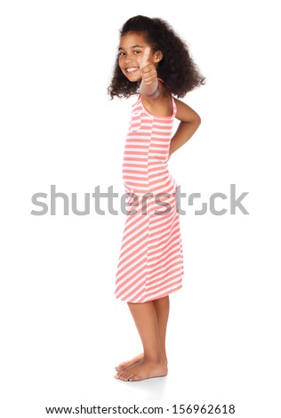 Adorable cute african child with afro hair wearing a white and pink striped dress. The girl is showing a thumbs up to the camera.