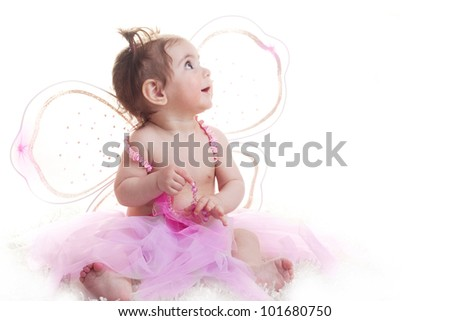 Adorable cute baby girl dressed as a fairy, princess, angel or ballerina sitting on white background looking at copy-space - stock photo