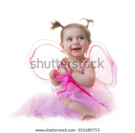 Adorable cute baby girl dressed as a fairy, princess, angel or ballerina sitting on white background looking at copy-space
