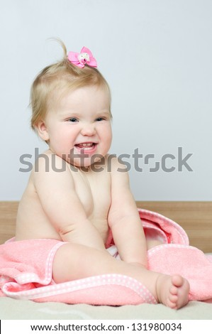 Adorable cute baby girl with pink towel after bath - stock photo