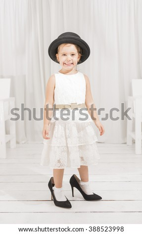 Adorable cute caucasian girl wearing white dress, black hat and black high heel shoes. Little girl trying to walk with big high heel shoes. Little girl fashionista in her mother's big heeled shoes - stock photo
