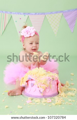 Adorable cute laughing blond hair baby girl with flower head band in pink tutu grabbing vanilla sponge cake with pink and purple heart icing while sitting on green background with flag bunting behind