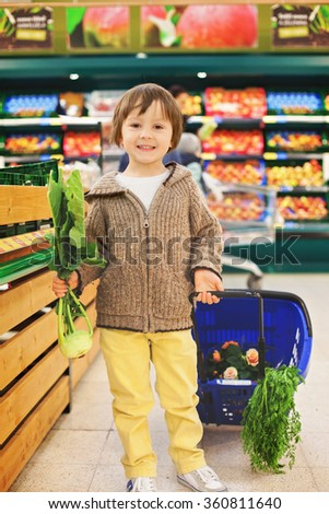 Adorable cute little and proud boy helping with grocery shopping, healthy lifestyle concept - stock photo
