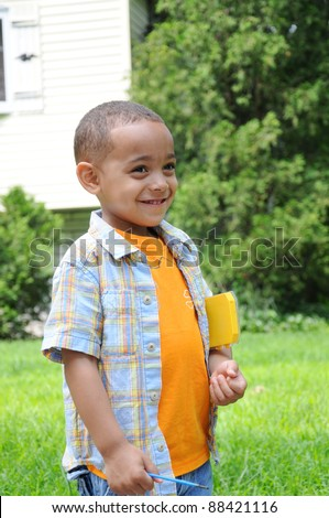 Adorable Cute Little Boy Smiling looking away standing outside during daytime holding object under arm