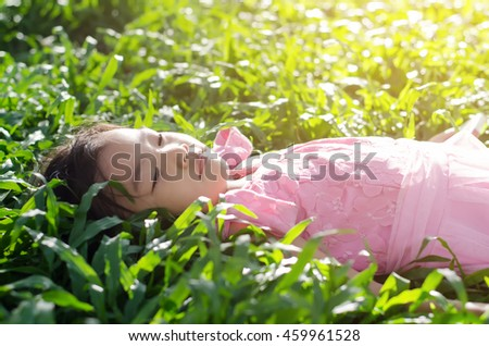 Adorable cute little girl lying on the grass,vintage style.