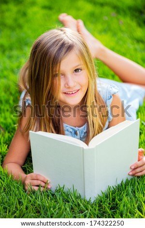 Adorable cute little girl reading book outside on grass - stock photo