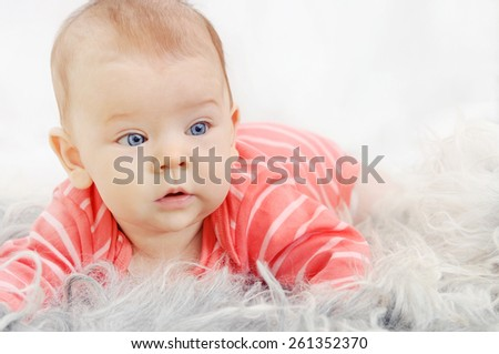 adorable cute little girl with big blue eyes and wide smile playing on the white sofa - stock photo