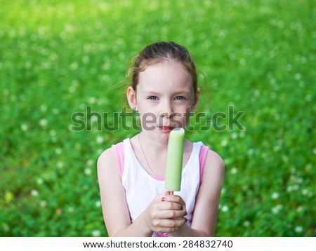 Adorable cute pretty little girl playing outdoors in summer and eating ice cream. Happy childhood. - stock photo