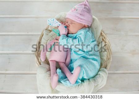 adorable cute sweet baby girl sleeping in white basket on wooden floor hugging tilda rabbits  - stock photo