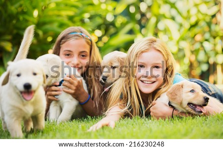 Adorable Cute Young Girls with Golden Retriever Puppies - stock photo