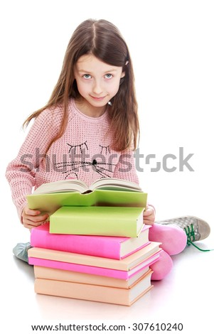 Adorable dark haired slender girl of school age in a pink knitted sweater reading a book . Girl sitting on the floor putting his feet under him . Re girl is a stack of books-Isolated on white - stock photo