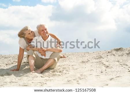 Adorable elderly couple went to the beach to enjoy the sea breeze - stock photo