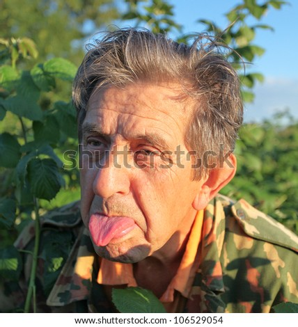 Adorable elderly man with tongue outdoor - stock photo