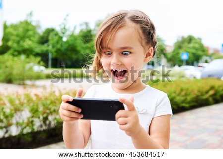Adorable expressive little girl with a smartphone outdoors