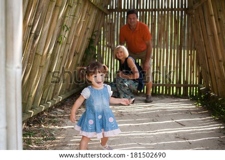Adorable family are having fun in bamboo house in the park - stock photo