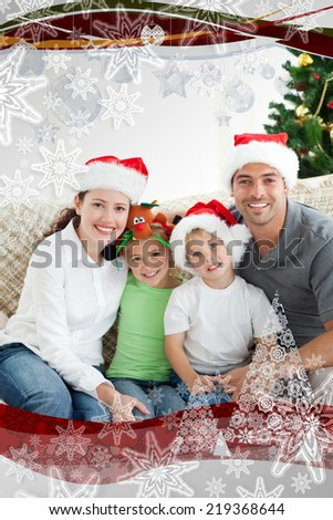 Adorable family at Christmas sitting in the livingroom with christmas frame - stock photo