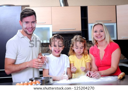 Adorable family baking together in the kitchen to make delicious cookies - stock photo
