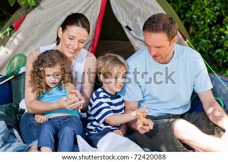 Adorable family camping in the garden - stock photo