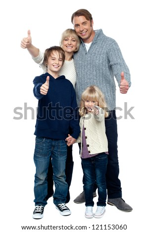 Adorable family in winter clothes gesturing thumbs up. Full length portrait over white background. - stock photo