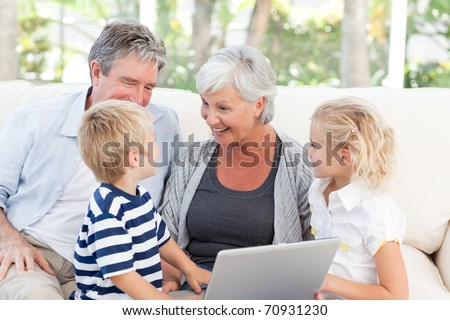 Adorable family looking at their laptop - stock photo