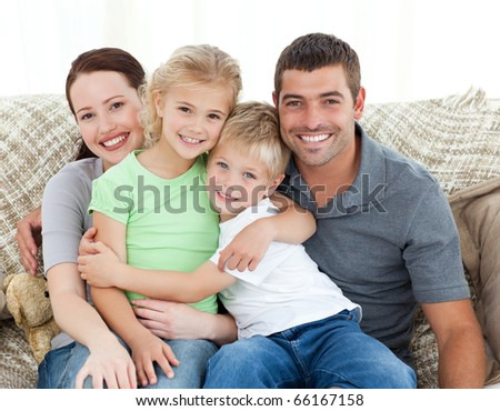 Adorable family sitting on the sofa and smiling at the camera
