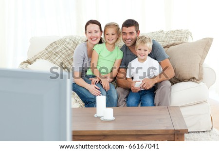 Adorable family watching television together sitting on the sofa at home