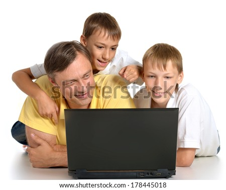 Adorable family with laptop lying on the floor - stock photo