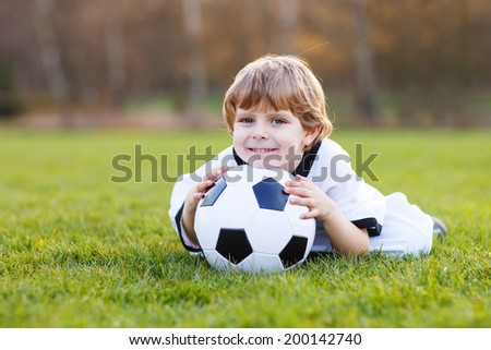 Adorable fan boy at public viewing of soccer or football game, outdoors
