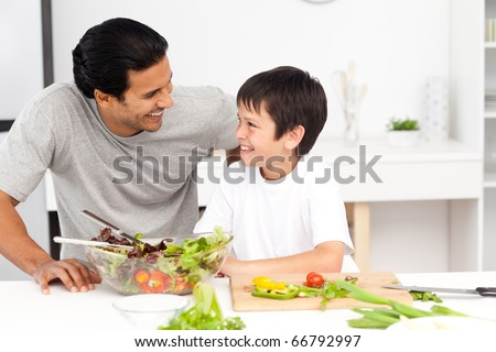 Adorable father and son looking at each other in the kitchen at home