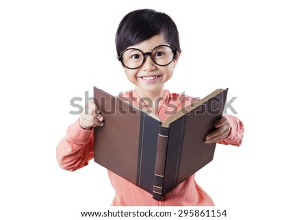 Adorable female student wearing casual clothes and glasses in the studio while holding and read a book - stock photo