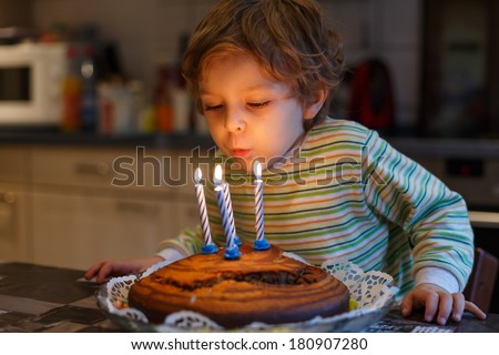 Adorable four year old boy celebrating his birthday and blowing  - stock photo