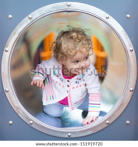 Adorable funny baby girl hiding on a playground - stock photo