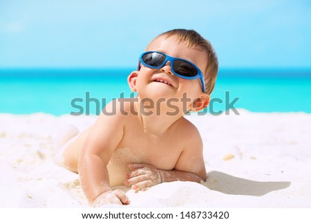 Adorable funny baby with sunglasses lying on the white sandy beach and enjoying his first tropical vacation at Maldives - stock photo