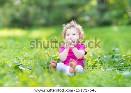 Adorable funny curly baby girl eating candy in a sunny park - stock photo