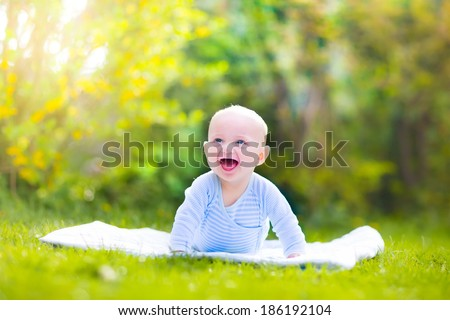 Adorable funny laughing baby boy in a blue shirt playing on his tummy relaxing on a white blanket in a green summer garden on a sunny morning - stock photo